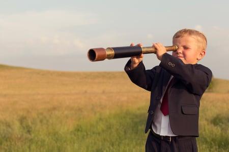 Young-Boy-Businessman-Looking-through-Telescope-491428626_2125x1416.jpeg
